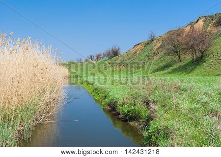 Landscape with small Ukrainian river Sura at early spring season