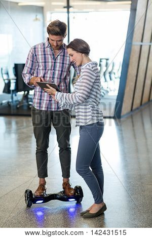 Man on hoverboard using digital tablet with colleagues in office