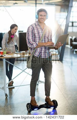 Portrait of smiling man standing on hoverboard and using laptop in office