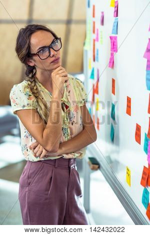 Thoughtful woman looking at sticky notes in office