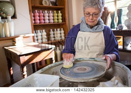 Female potter cleaning pottery wheel in pottery workshop