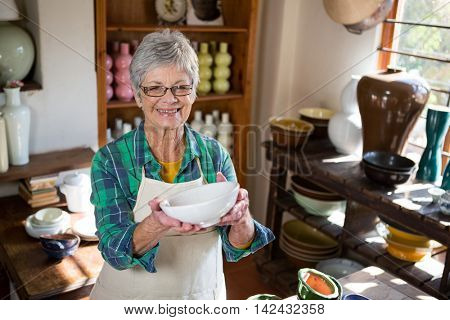 Happy female potter holding bowl in pottery workshop
