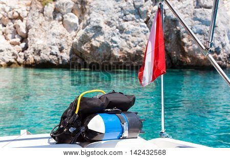 Divers flag with scuba diving equipment laying on a boat