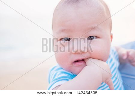 cute baby smile happily in adult arms in the beachasian