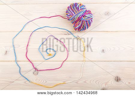Multicolor bundle lie on wooden table surface. Its thread forms interesting design. Knot on end of thread. Top view.