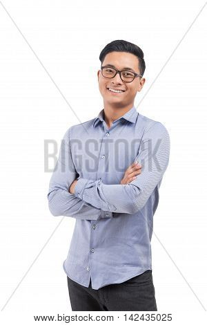 Smiling Asian man in glasses blue shirt and black pants standing with hands folded. Concept of engineering jobs