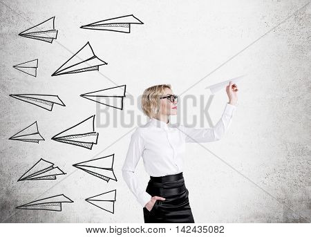 Blond woman in glasses is holding paper plane in her hand. Sketch of other planes on concrete wall. Concept of decision making.