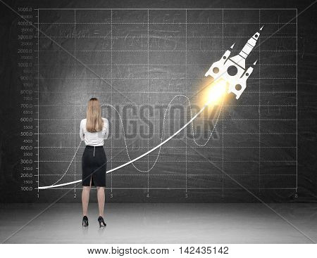 Rear view of woman in business suit examining sinusoid graph with launching rocket image on it. Concept of data analysis