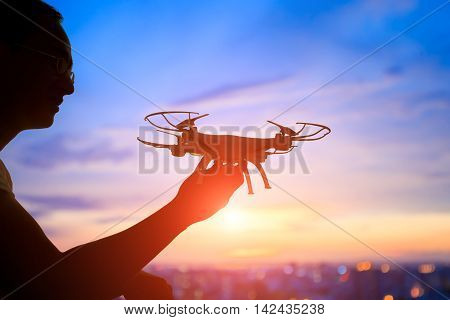 silhouette of man play drone in the sunset asian