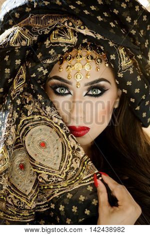 Portrait of a beautiful female model in a striking head turban with piercing eyes and red lips in an arabian style