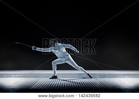 Fencing player isolated on the black background