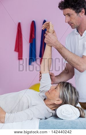 Physiotherapist massaging a senior womans hand in clinic
