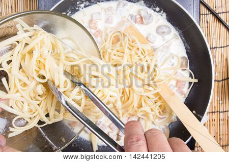 Chef putting Spaghetti carbonara to pan with tongs / cooking spaghetti concept