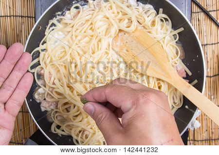 Chef putting pasrley to the pan cooking spaghetti carbonara / cooking spaghetti concept /selective focus