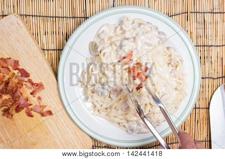decorated Spaghetti carbonara with cryspy bacon / cooking spaghetti concept
