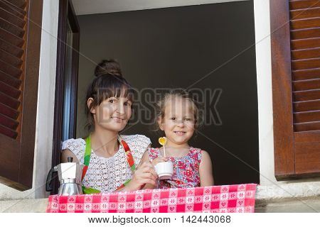Two years old girl with mother are sitting on window sill with traditional European wood brown shutters