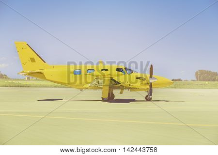 Yellow propeller plane parking at the airport. Sunny day.