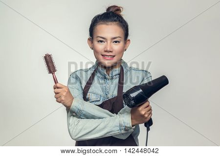 Asia woman was holding a hairdryer and brush.