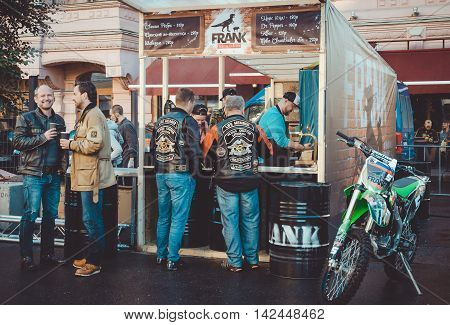 Saint-Petersburg Russia - August 11-14 2016: Bikers from all over Europe on Nevsky prospect during annual European Bike festival Harley Davidson Days best motorcycle events. Tourist mans eating drinks in street food restaurant Frank meat. Lifestyle concep