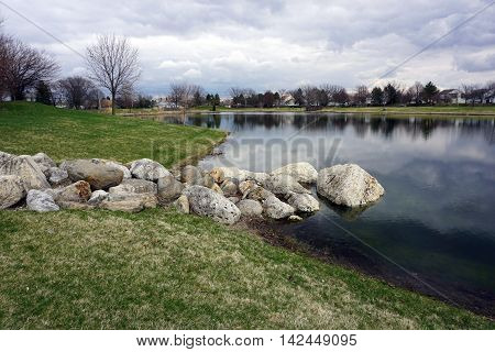 A pile of large rocks on the shore of a small, man-made lake in the Wesmere Country Club subdivision of Joliet, Illinois during the Spring.