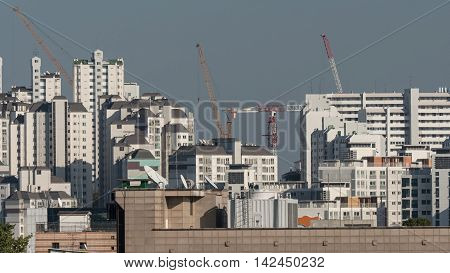 View of the typical high-rise apartment blocks and construction cranes in Seoul, South Korea