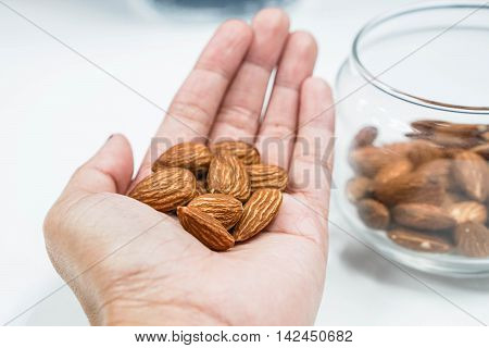 Holding some almonds in human left hand with selective focus