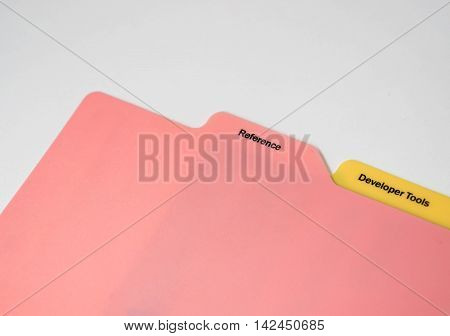 Pink and yellow plastic book mark for reference and development tools