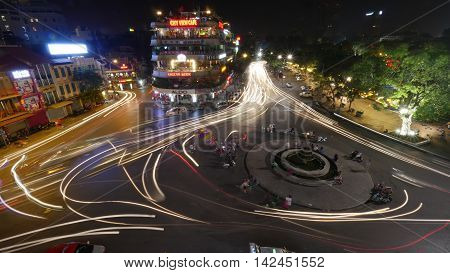 HANOI, VIETNAM - OCTOBER 27, 2015: Transport traffic with illuminated motion traces around the fountain on the square in city centre