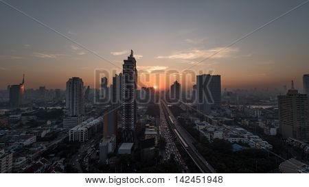 Sunset time in Bangkok, Thailand. City panorama with highrise urban architecture and traffic on highway. Sky in warm colors and sun going down