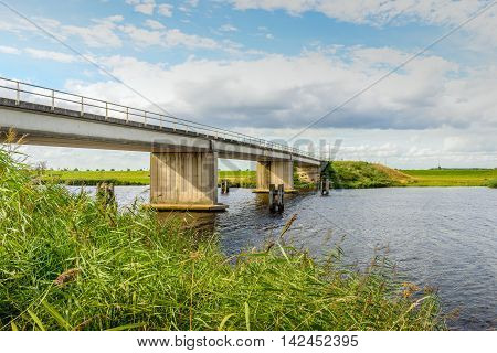 Concrete bridge in a rural area in the Netherlands. It's a sunny day in the summer season with a blue sky with some clouds.