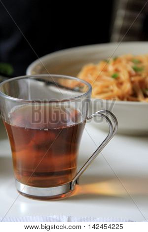 Clear glass of hot flavored tea, with bowl of noodles for lunch.