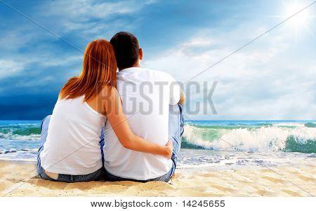 Vista al mar de una pareja sentada en la playa.