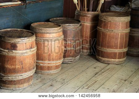 Several wood wine barrels lined up against wall of barn