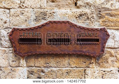 antique rusted mailbox at an old stone house in an Italian town