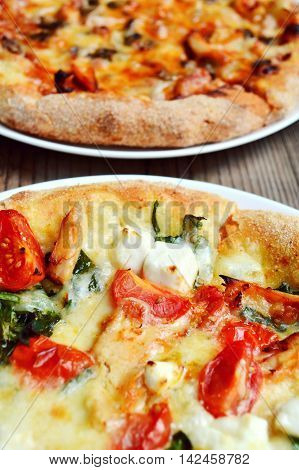 Big hot pizza with tomatoes, feta cheese and spinach and dig hot pizza with tomatoes, mushrooms and cheese