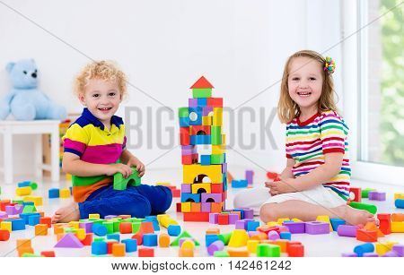 Happy preschool age children play with colorful plastic toy blocks. Creative kindergarten kids build a block tower. Educational toys for toddler or baby. Siblings having fun playing together.