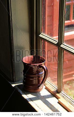 Large clay mug on windowsill of home