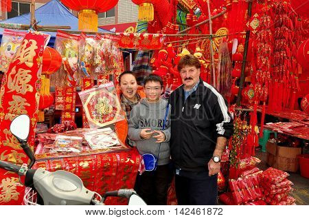 Pengzhou China - February 3 2013: Happy mother and her son selling decorations for the Chinese Lunar New Year holiday pose with a western tourist