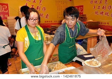 Chengdu China - September 15 2010: Two workers selling food at the 10th Chinese Moon Cake Festival at the annual Sichuan and Tianfu Food Fair
