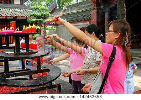 Chengdu China - April 25 2005: Women lighting incense sticks from a brazier of burning red candles in a courtyard of the Wenshu Buddhist Temple at the Manjursi Monastery