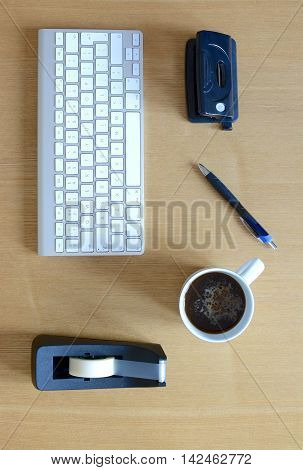 Wooden desktop view with keyboard, pen, hole punch, sellotape and a mug of coffee