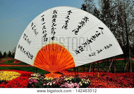 Qingbaijiang China - October 28 2010: Chinese fan with quotations from Chairman Mao Zedong sits amidst displays of mums Salvia and Marigolds at the annual Phoenix Lake Park Chrysanthemum Exposition