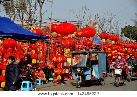 Pengzhou China - January 21 2014: Bright red lanterns and other Chinese New Year decorations sold by vendors line the street in the Long Xing outdoor marketplace
