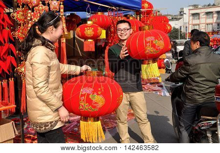 Pengzhou China - January 21 2014: Man and woman holding large red lanterns at their stall where they sell items for the Chinese Lunar New Year