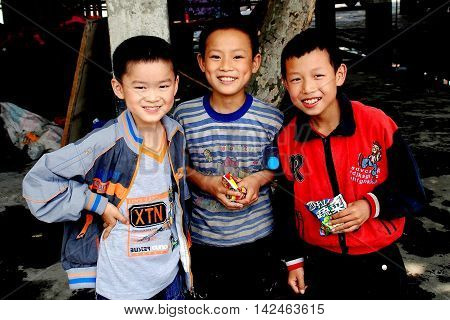 Wan Jia China - June 11 2008 Three smiling schoolboys eating packaged food snacks in the village marketplace