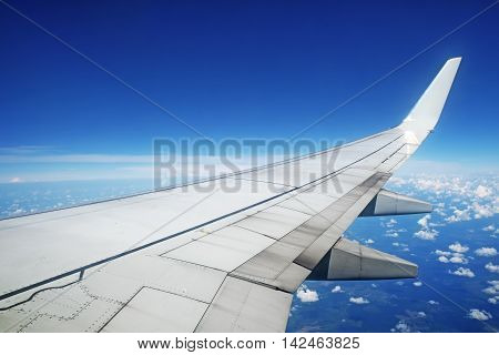 Aircraft wing in flight on blue sky background