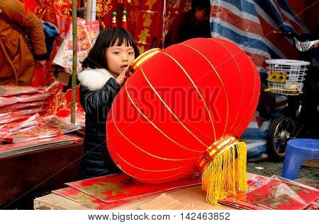 Pengzhou China - January 29 2014: Little Chinese girl holding a big red Chinese New Year lantern at a vendor's booth in Long Xing Square