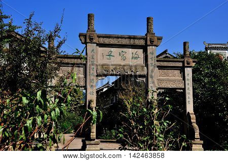 Xin Xing Zhen China - October 7 2013: Stone ceremonial gate inscribed with Chinese characters leads into the town's main street *