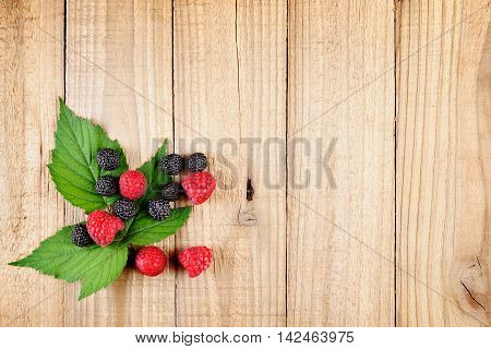 Red and black raspberries on wooden background