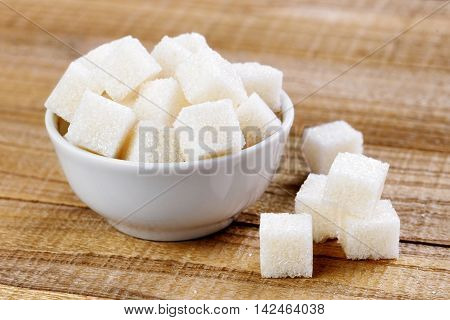 White sugar cubes in bowl on wooden table